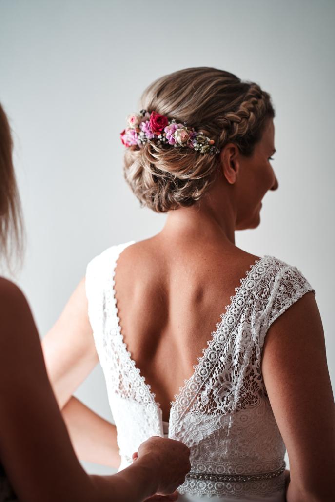 Hochzeitsfoto von Braut beim Anziehen des Brautkleides
