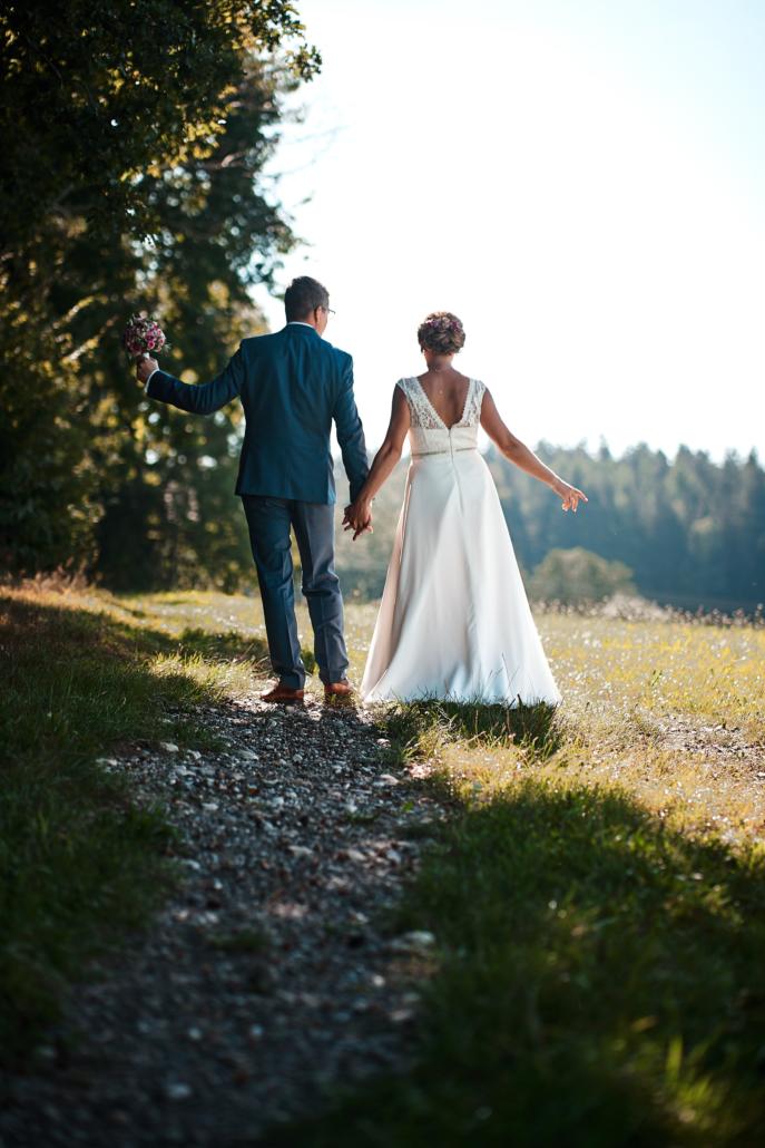 Hochzeitsfotos von Braut und Bräutigam auf einer sonnendurchfluteten Wiese