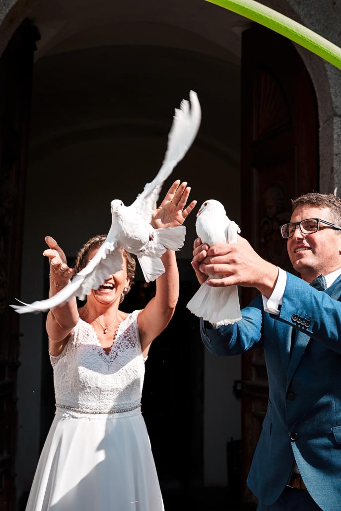 Hochzeitsfotos von Brautleuten die Taube freilassen nach Trauung