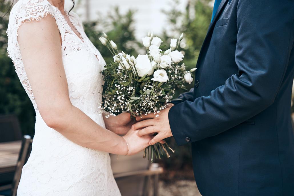 Brautleute halten Brautstrauß