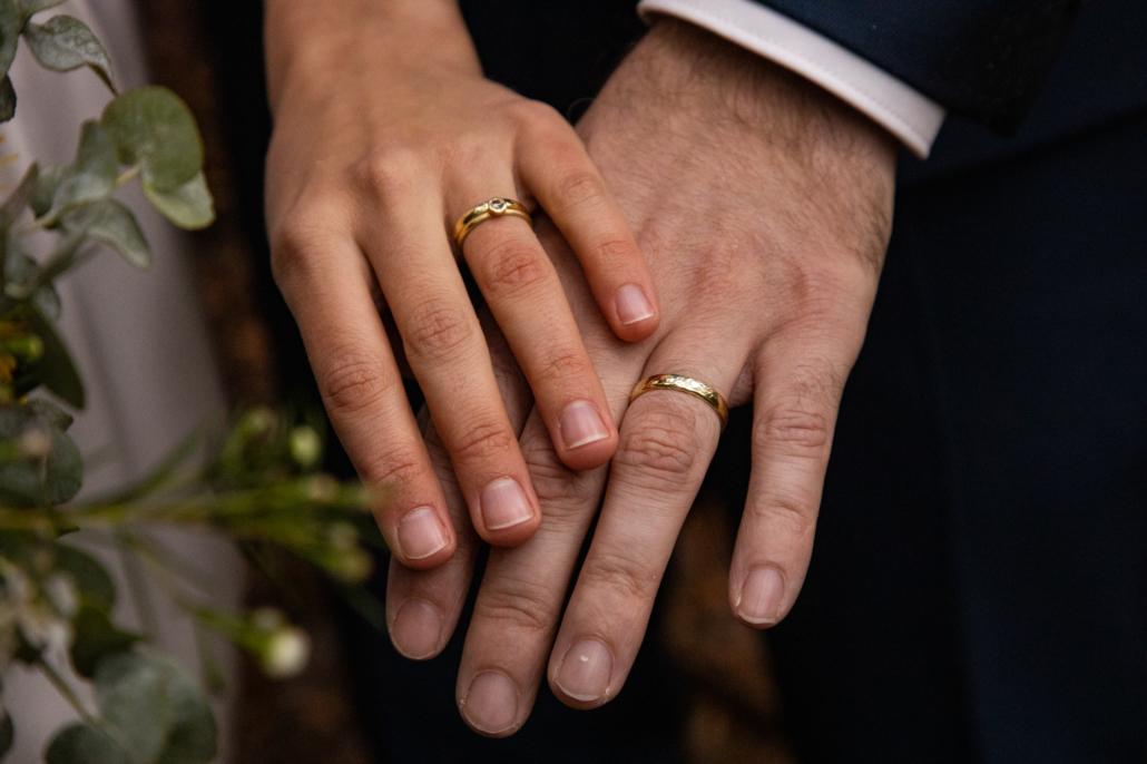 Hochzeitsfotos der Hände der Brautleute mit Eheringen